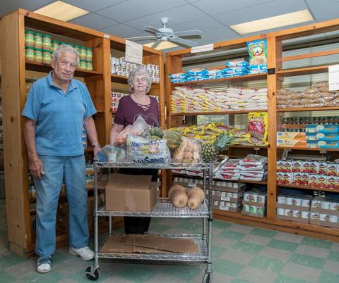 Two aduls age 60+, one man and one woman stand looking proud with lots of shelves of behind them full of boxed and canned food items.