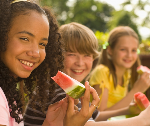 3 kids approximate 8-10 years old, 1 black girl wearing pink with long curls, one little boy white, white with shaggy, sandy colored hair, one girl white with sandy colored hair in pigtails, all looking at the camera and smiling with watermelon in their hands.