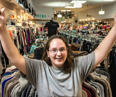 A young woman approximately in her early to mid 20's stands infront of racks of clothes. She has long light brown hair and glasses. She stands with her arms triumphantly spread over her head with a smile on her face.