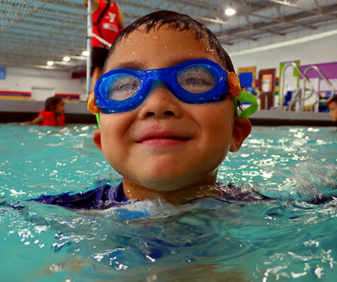 All boy approximate 5 years old smiles for the camera. He is in an indoor pool with blue swim goggles on. He has wet dark hair.