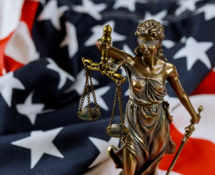 Photo of a statue of blind lady justice set against an American flag